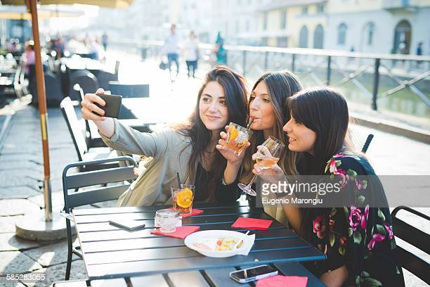 Three young women posing for smartphone selfie at waterfront cafe