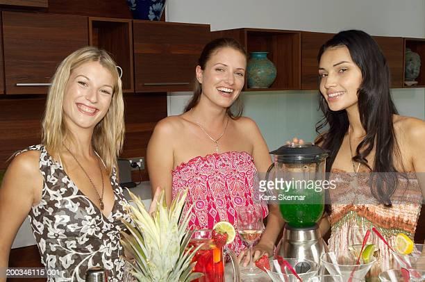 Three young women preparing cocktails in blender, portrait