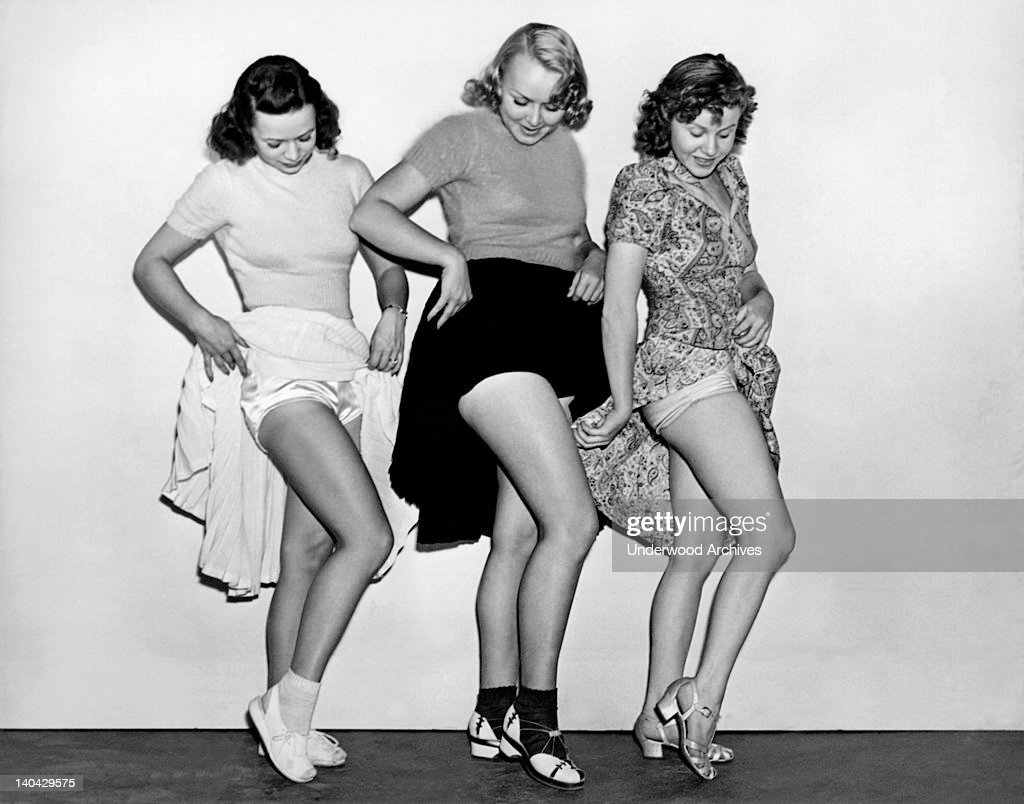 Three young women raise their skirts to compare either legs, underwear, or suntans, Hollywood, California, circa 1948.