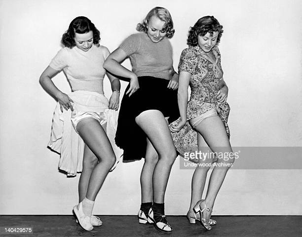 Three young women raise their skirts to compare either legs underwear or suntans Hollywood California circa 1948