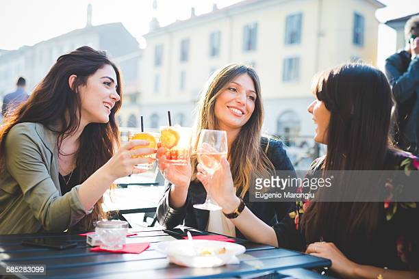 Three young women raising a toast at sidewalk cafe