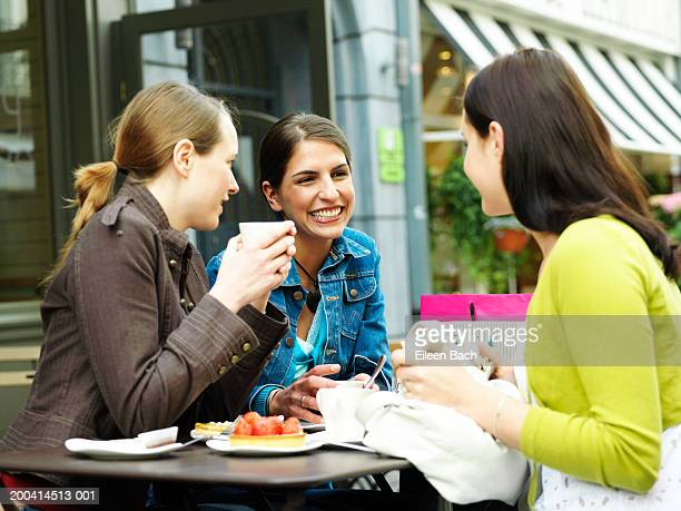 Three young women relaxing at outdoor cafe, smiling