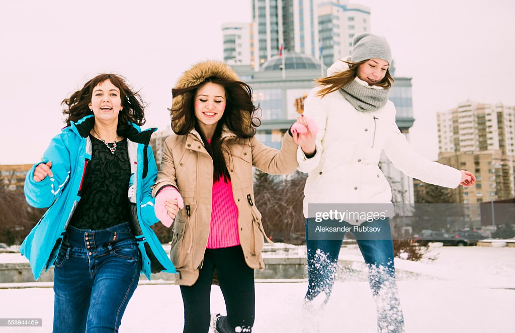 Three young women running in snow holding hands : Stock Photo