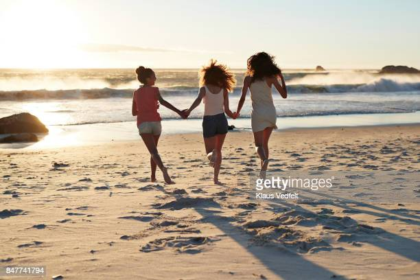 Three young women running towards the sea, hand in hand