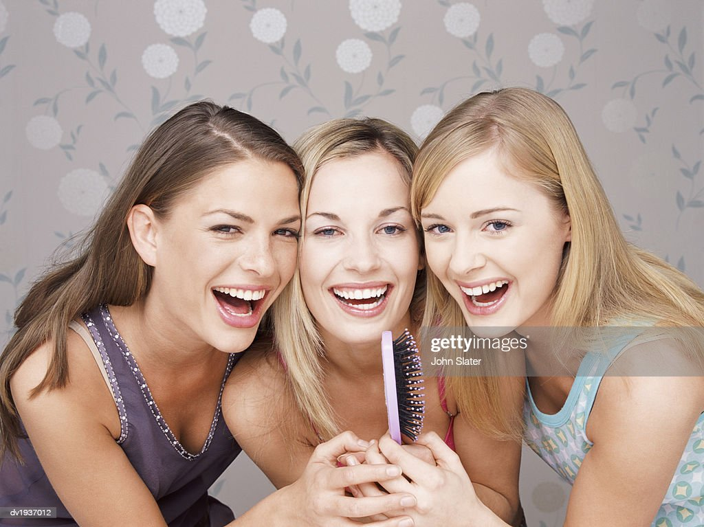 Three Young Women Singing Into a Hairbrush Together : Stock Photo