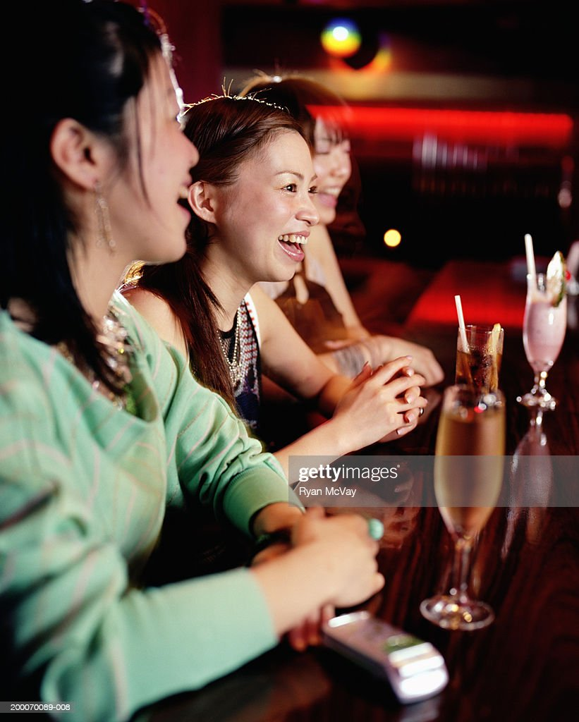Three young women sitting at bar, drinking cocktails, laughing : Stock Photo