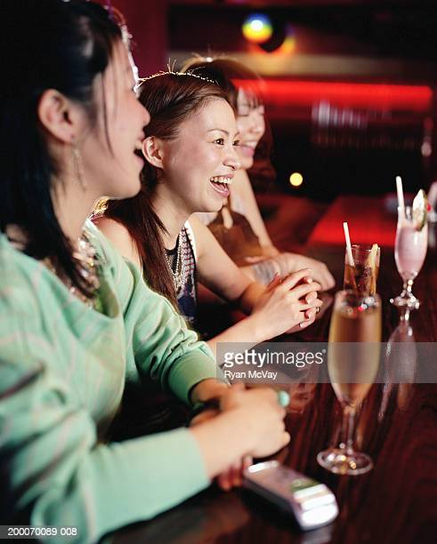 Three young women sitting at bar, drinking cocktails, laughing