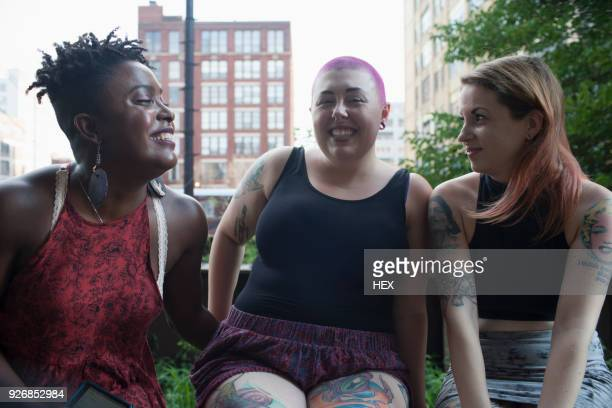 three young women sitting down - big fat white women stockfoto's en -beelden