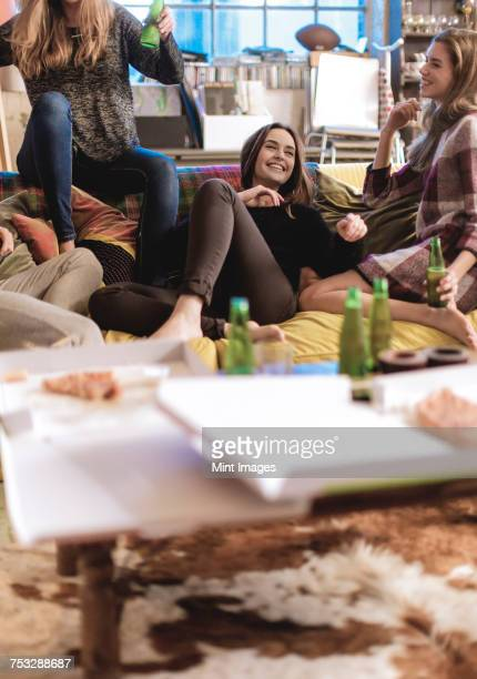 three young women sitting on a sofa, laughing, pizza and beer bottles on coffee table. - night in fotografías e imágenes de stock