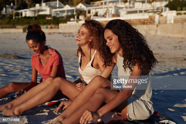 three young women sitting on beach and smiling - women sunbathing stock photos and pictures