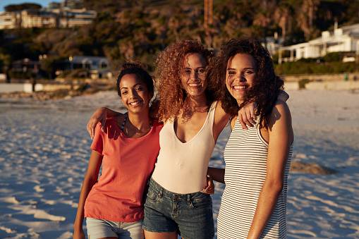 Three young women sitting on beach and smiling - gettyimageskorea
