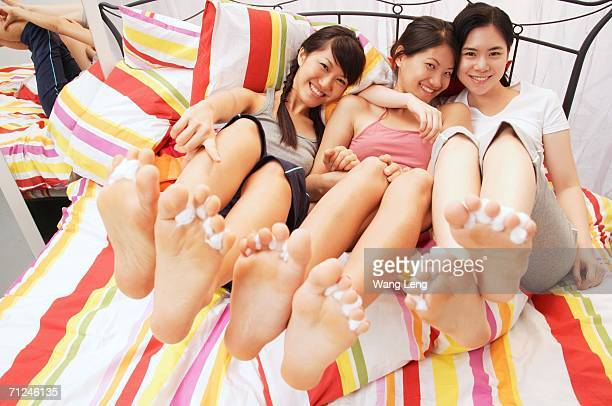Three young women sitting on bed, showing their feet to camera