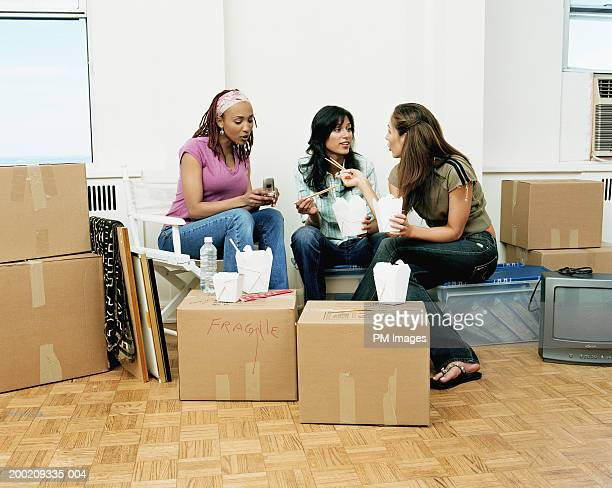 Three young women sitting on boxes in apartment eating and talking