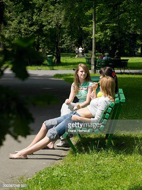 three young women sitting on park bench - rolled up trousers stock pictures, royalty-free photos & images