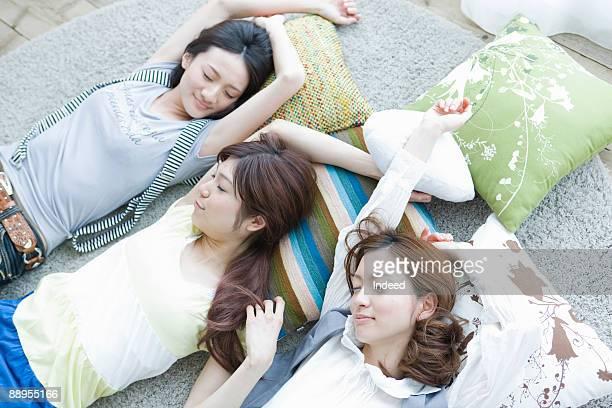 Three young women sleeping on floor