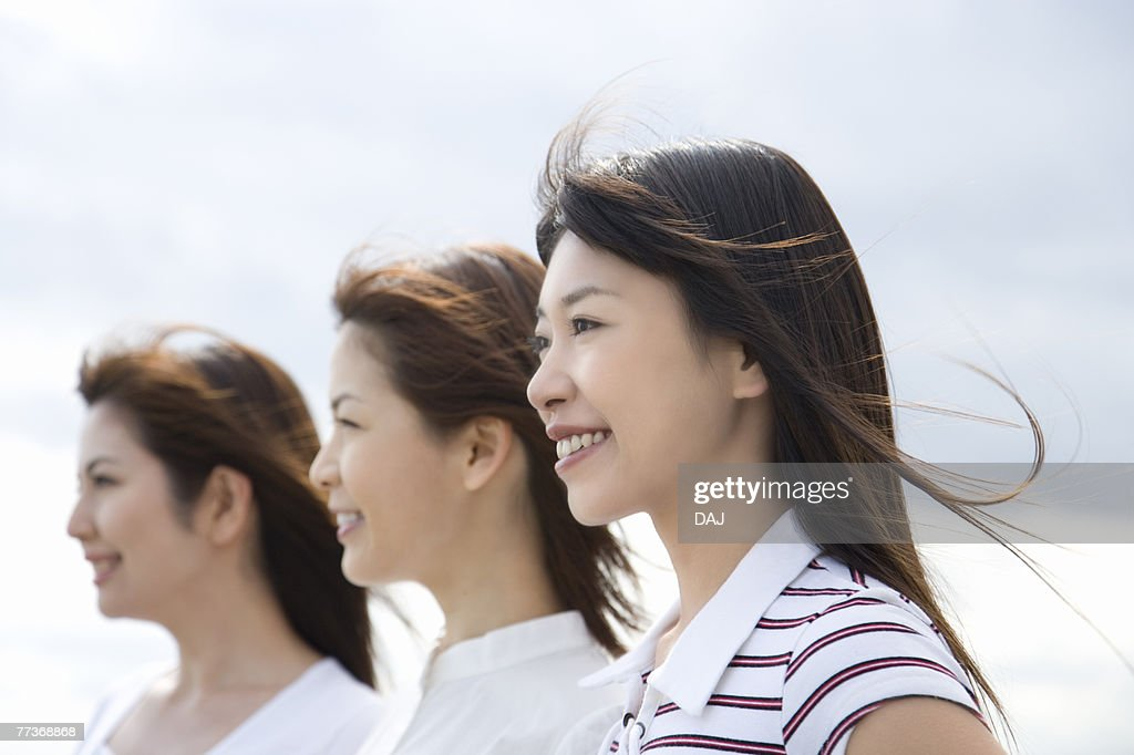 Three young women, smiling, side view : Photo