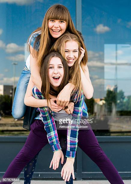 Three young women stacked on top of each other in city