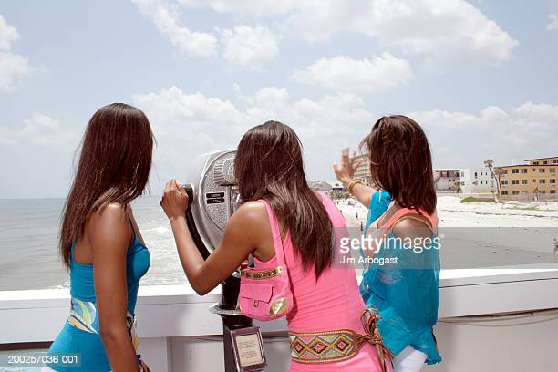 Three young women standing at coin-operated binoculars on beach