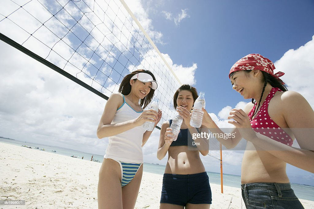 Three Young Women Standing by a Volleyball Net : Stock Photo