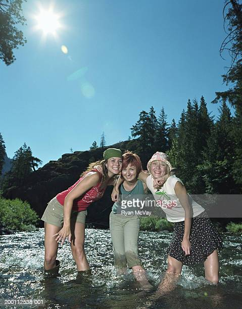 three young women standing in river with arms around each other - women in wet t shirts stock photos and pictures
