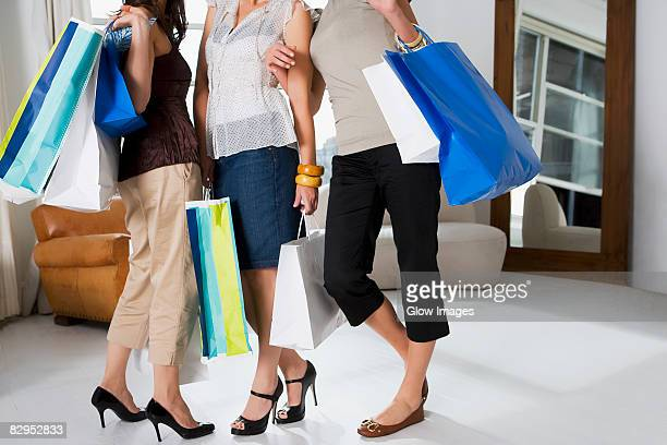 Three young women standing together and carrying shopping bags