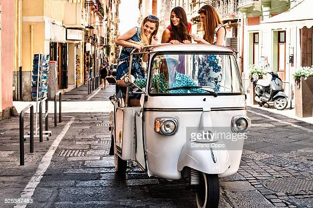 Three young women standing up in open back seat of Italian taxi, Cagliari, Sardinia, Italy
