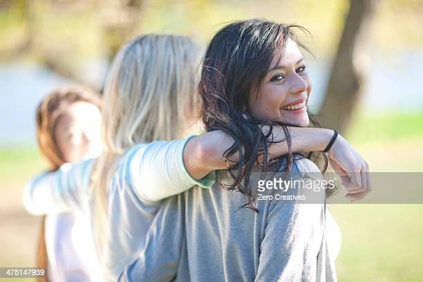 three young women strolling in park - passer le bras autour photos et images de collection