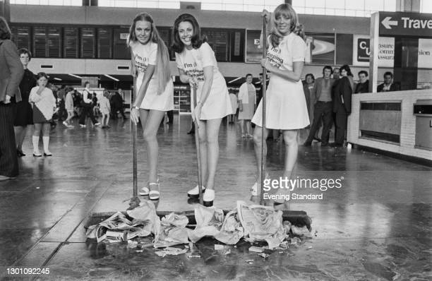 Three young women sweep litter at Euston Station in London, as part of the Keep Britain Tidy anti-litter campaign, UK, 16th July 1973.