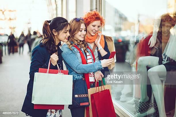 Three young women taking images while window shopping