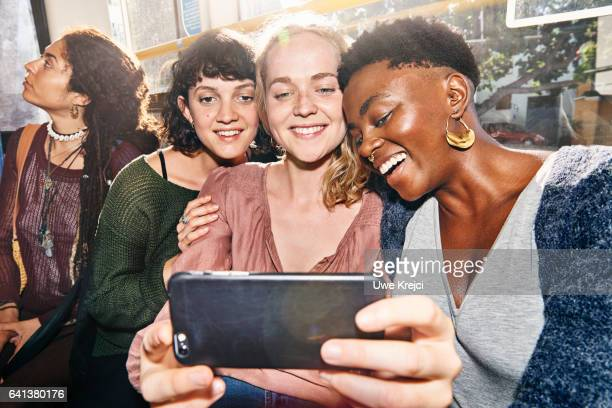 Three young women taking self portrait with smart phone on a bus