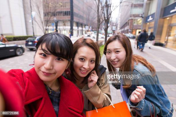 Three young women taking selfie pictures after shopping