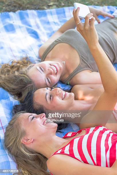 Three young women taking selfie with smart phone