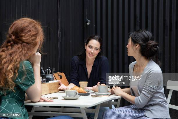 Three young women talking and enjoying coffee and lunch together