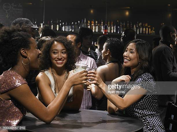 Three young women toasting with cocktails in nightclub, smiling