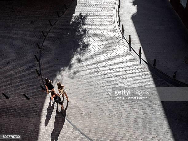 Three young women walking along a pedestrian street in summer