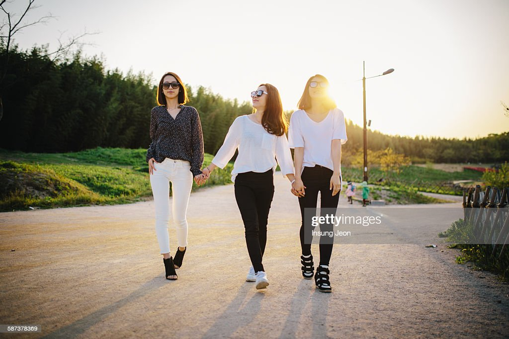 Three young women walking in park : Stock Photo