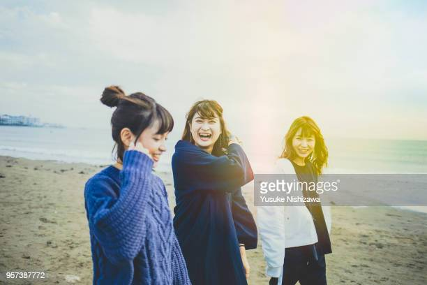 three young women walking together on sandy beach - exclusivamente japonés fotografías e imágenes de stock