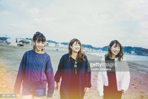 three young women walking together on sandy beach - 3人 ストックフォトと画像