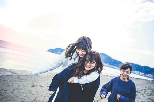 Three young women walking together on sandy beach - gettyimageskorea