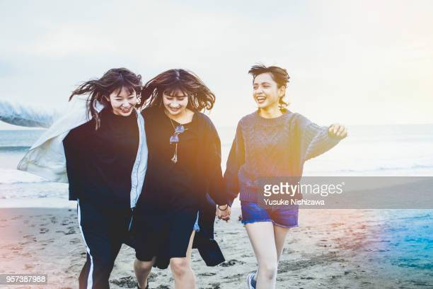 Three young women walking together on sandy beach