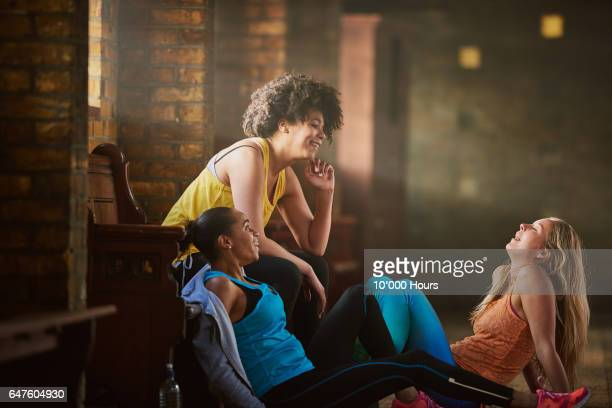 three young women wearing sports clothing talking in gym. - small group of people stock pictures, royalty-free photos & images