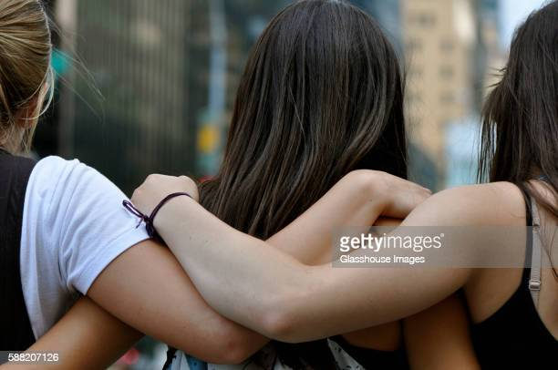 three young women with arms around each other, close up, rear view - schulter stock-fotos und bilder