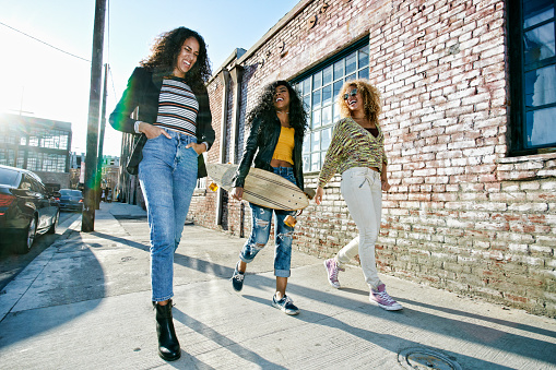 Three young women with long curly hair walking along pavement, one carrying skateboard. - gettyimageskorea
