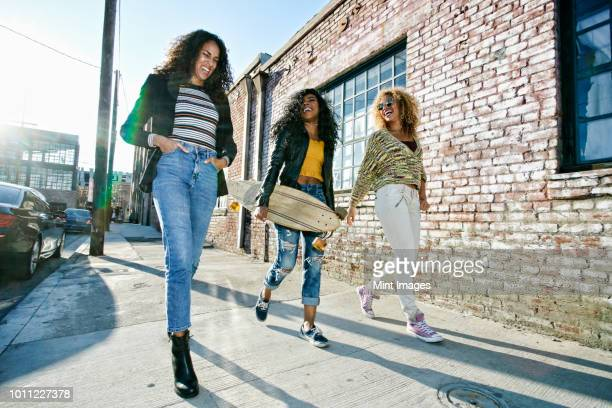three young women with long curly hair walking along pavement, one carrying skateboard. - moda foto e immagini stock
