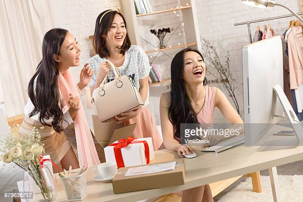Three young women with online purchases