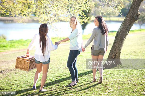 Three young women with picnic basket in park