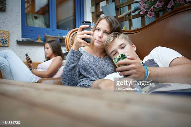 Three youth sitting on a couch staying outside in the garden on August 10 2015 in Bonn Germany