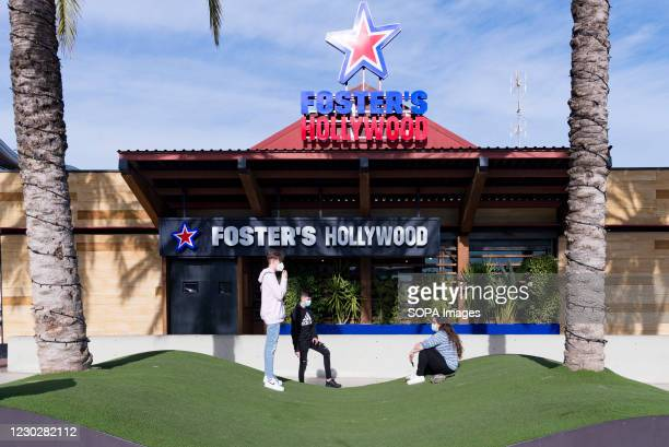 Three youth wearing face masks are in front of a branch of the fast food restaurant Foster's Hollywood at the Bonaire shopping center.