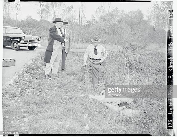 Three Youths Murdered Chicago Illinois Cook County coroner Walter McCarran points to the nude bodies of three youths found in this ditch in Robertson...