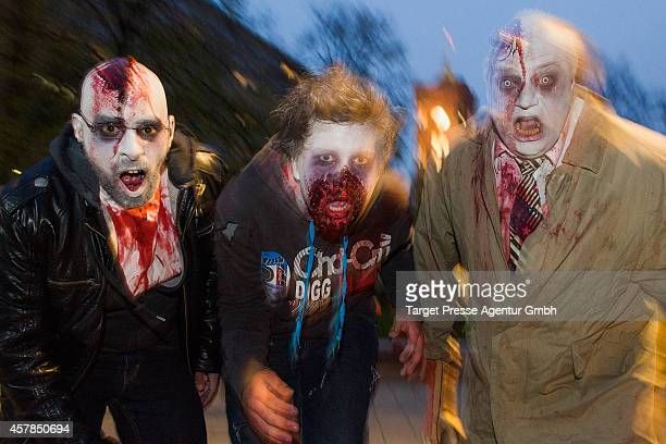 Three zombie enthusiasts walk over the Alexanderplatz as part of a flashmob on October 25 2014 in Berlin Germany Over 150 participants dressed as...